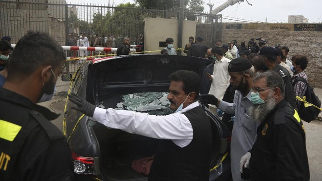 Security personnel check a car used by attackers at the Stock Exchange Building in Karachi, Pakistan, Monday, June 29, 2020. Gunmen attacked the stock exchange on Monday. Special police forces deployed to the scene of the attack and in a swift operation secured the building. (AP Photo/Fareed Khan)