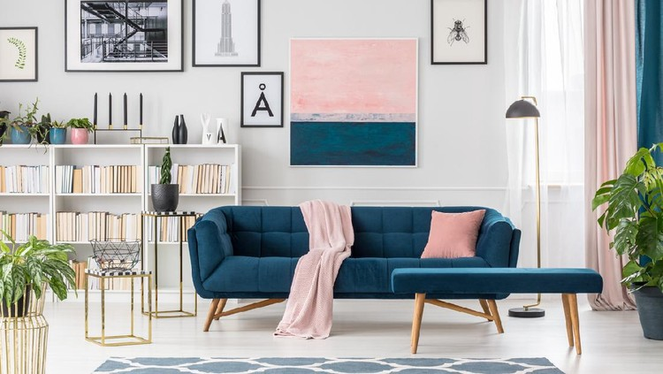 Blue bench and settee with pink blanket in elegant living room interior with bookshelf and posters
