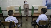 A teacher in protective gear teaches her students, seated at partitioned desks at the Samkhok School in Pathum Thani, outside Bangkok, Wednesday, July 1, 2020. Thailand has begun a fifth phase of relaxations of COVID-19 restrictions, allowing the reopening of schools and high-risk entertainment venues such as pubs and massage parlors that had been shut since mid-March. (AP Photo/Sakchai Lalit)
