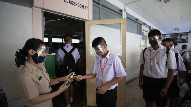 Teacher in protective gear offers hand sanitizer to students before class at the Samkhok School in Pathum Thani, outside Bangkok, Wednesday, July 1, 2020. Thailand has begun a fifth phase of relaxations of COVID-19 restrictions, allowing the reopening of schools and high-risk entertainment venues such as pubs and massage parlors that had been shut since mid-March. (AP Photo/Sakchai Lalit)