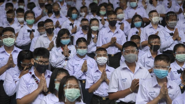 Students wearing protective gear to help curb the spread of the coronavirus pray before class at the Samkhok School in Pathum Thani, outside Bangkok, Wednesday, July 1, 2020. Thailand has begun a fifth phase of relaxations of COVID-19 restrictions, allowing the reopening of schools and high-risk entertainment venues such as pubs and massage parlors that had been shut since mid-March. (AP Photo/Sakchai Lalit)