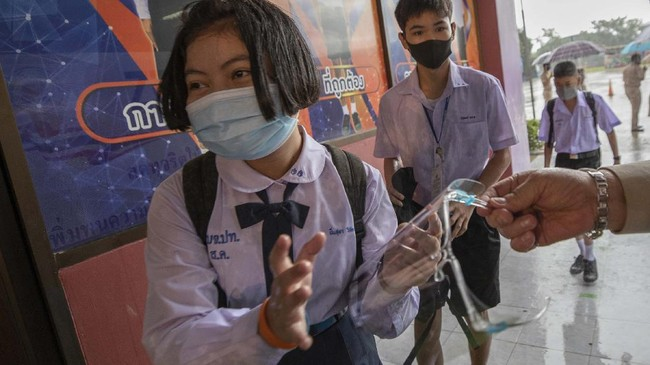 A teacher gives a face shield to a student at Samkhok School in Pathum Thani, outside Bangkok, Wednesday, July 1, 2020. Thailand has begun a fifth phase of relaxations of COVID-19 restrictions, allowing the reopening of schools and high-risk entertainment venues such as pubs and massage parlors that had been shut since mid-March. (AP Photo/Sakchai Lalit)