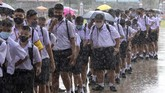 Students wearing a face mask to help curb the spread of the coronavirus as they arrive at Samkhok School during rain in Pathum Thani, outside Bangkok, Wednesday, July 1, 2020. Thailand has begun a fifth phase of relaxations of COVID-19 restrictions, allowing the reopening of schools and high-risk entertainment venues such as pubs and massage parlors that had been shut since mid-March. (AP Photo/Sakchai Lalit)