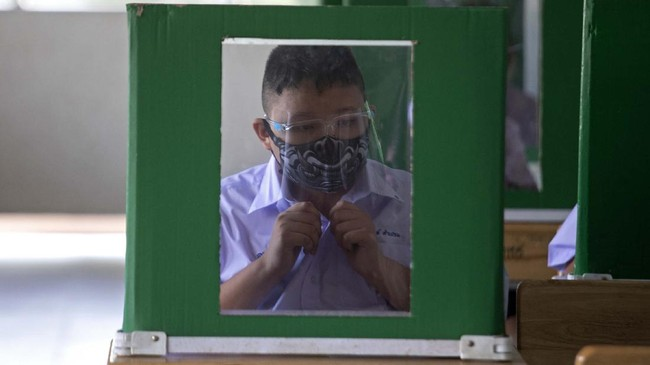 Student in a protective mask and a face shield sits, maintaining social distancing and partitioned spaces at Samkhok School in Pathum Thani, outside Bangkok, Wednesday, July 1, 2020. Thailand has begun a fifth phase of relaxations of COVID-19 restrictions, allowing the reopening of schools and high-risk entertainment venues such as pubs and massage parlors that had been shut since mid-March. (AP Photo/Sakchai Lalit)
