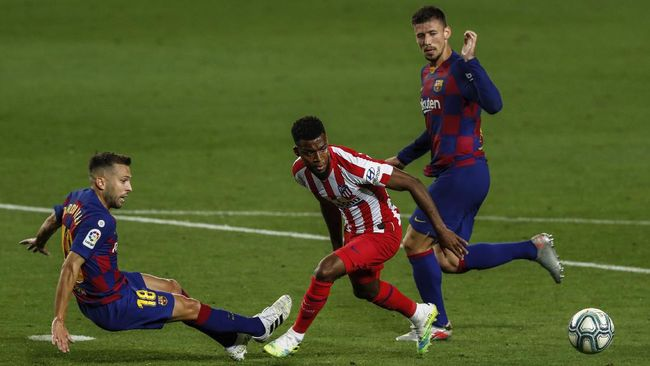 Atletico Madrid's Thomas Lemar, center, views for the ball next to Barcelona's Jordi Alba, left, and Barcelona's Clement Lenglet, right, during the Spanish La Liga soccer match between FC Barcelona and Atletico Madrid at the Camp Nou stadium in Barcelona, Spain, Tuesday, June 30, 2020. (AP Photo/Joan Monfort)