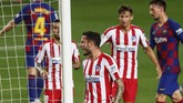 Atletico Madrid's Saul, center, celebrates after scoring his side's second goal during the Spanish La Liga soccer match between FC Barcelona and Atletico Madrid at the Camp Nou stadium in Barcelona, Spain, Tuesday, June 30, 2020. (AP Photo/Joan Monfort)