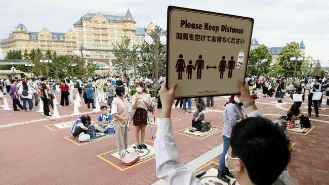 People wearing face masks to protect against the spread of the new coronavirus demonstrate the social distancing before they wait to enter Tokyo Disneyland in Urayasu, near Tokyo, Wednesday, July 1, 2020. Tokyo Disneyland reopens for the first time in four months after suspending operations due to coronavirus concerns. (Kyodo News via AP)