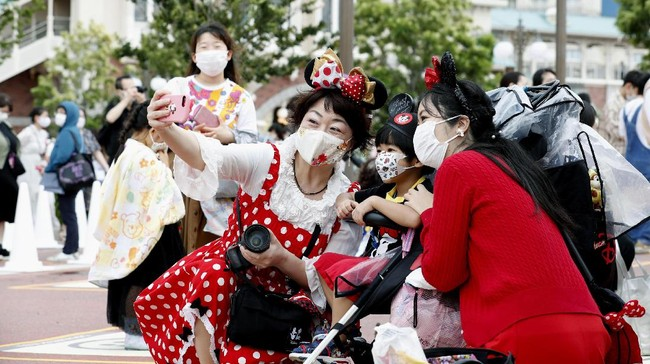 People wearing face masks to protect against the spread of the new coronavirus take a selfie together before they wait to enter Tokyo Disneyland in Urayasu, near Tokyo, Wednesday, July 1, 2020. Tokyo Disneyland reopens for the first time in four months after suspending operations due to coronavirus concerns. (Kyodo News via AP)