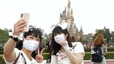 Visitors wearing face masks to protect against the spread of the new coronavirus take a selfie at Tokyo Disneyland in Urayasu, near Tokyo, Wednesday, July 1, 2020. Tokyo Disneyland reopens for the first time in four months after suspending operations due to coronavirus concerns. (Kyodo News via AP)