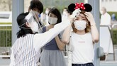 A visitor has her body temperature checked at the entrance of Tokyo Disneyland in Urayasu, near Tokyo, Wednesday, July 1, 2020. Tokyo Disneyland reopened for the first time in four months after suspending operations due to coronavirus concerns. (Kyodo News via AP)
