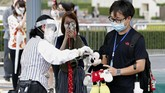 A visitor gestures to have the body temperature of a Mickey Mouse doll checked at the entrance of Tokyo Disneyland in Urayasu, near Tokyo, Wednesday, July 1, 2020. Tokyo Disneyland reopened for the first time in four months after suspending operations due to coronavirus concerns. (Kyodo News via AP)