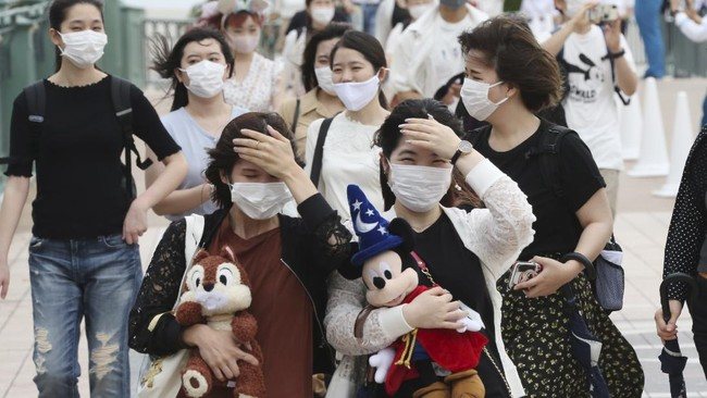 People wearing face masks to protect against the spread of the new coronavirus walk toward the entrance to Tokyo Disneyland in Urayasu, near Tokyo, Wednesday, July 1, 2020. Tokyo Disneyland reopens for the first time in four months after suspending operations due to coronavirus concerns. (AP Photo/Koji Sasahara)