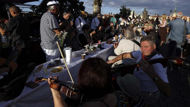 Residents play music as they sit to dine on a 500 meter long table set on the medieval Charles Bridge, after restrictions were eased following the coronavirus pandemic in Prague, Czech Republic, Tuesday, June 30, 2020. (AP Photo/Petr David Josek)