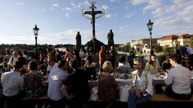 Residents sit to dine on a 500 meter long table set on the medieval Charles Bridge, after restrictions were eased following the coronavirus pandemic in Prague, Czech Republic, Tuesday, June 30, 2020. (AP Photo/Petr David Josek)