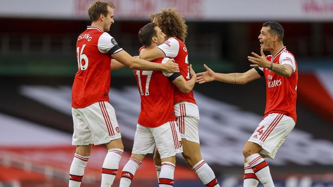 Arsenal's Cedric Soares, second left, is congratulated by teammates after scoring his side fourth goal during the English Premier League soccer match between Arsenal and Norwich City at the Emirates Stadium in London, England, Wednesday, July 1, 2020. (Richard Heathcote/Pool via AP)