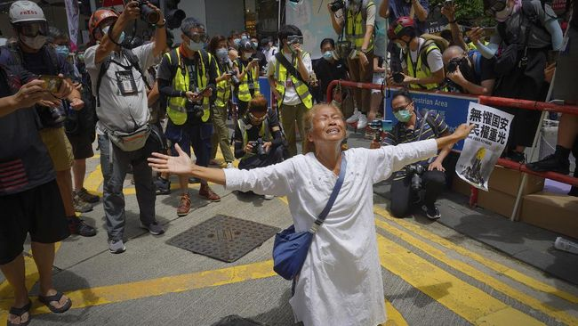 A woman prays in front of police at Causeway Bay before the annual handover march in Hong Kong, Wednesday, July 1, 2020. Hong Kong marked the 23rd anniversary of its handover to China in 1997, one day after China enacted a national security law that cracks down on protests in the territory. (AP Photo/Vincent Yu)