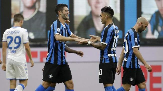 Inter Milan's Roberto Gagliardini, left, celebrates with his teammate Lautaro Martinez, second from right, after scoring his side's fourth goal during the Serie A soccer match between Inter Milan and Brescia at the San Siro Stadium, in Milan, Italy, Wednesday, July 1, 2020. (AP Photo/Luca Bruno)