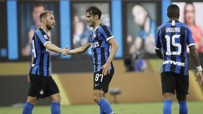Inter Milan's Antonio Candreva, center, celebrates with his teammate Christian Eriksen, left, after scoring his side's sixth goal during the Serie A soccer match between Inter Milan and Brescia at the San Siro Stadium, in Milan, Italy, Wednesday, July 1, 2020. (AP Photo/Luca Bruno)