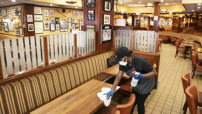 Imani Williams sanitizes tables at Junior's Restaurant, Monday, June 29, 2020, in New York. The Brooklyn restaurant is open for takeout service and outdoor dining only. Phase 3, allowing limited indoor dining, is scheduled to begin Monday, July 6, but Gov. Andrew Cuomo has indicated he may delay its implementation. (AP Photo/Mark Lennihan)