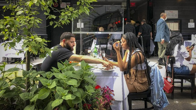 Diners eat al fresco due to COVID-19 concerns in midtown Manhattan, Friday, June 26, 2020, in New York. New York City Mayor Bill de Blasio says he's delaying the planned resumption of indoor dining at restaurants in the city out of fear it would ignite a spike in coronavirus infections. (AP Photo/John Minchillo)