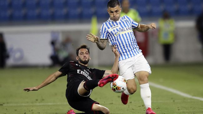 AC Milan's Hakan Calhanoglu, left, battles for the ball with Spal's Gabriel Strefezza during an Italian Serie A soccer match between Spal and Milan at the Paolo Mazza stadium in Ferrara, Italy, Wednesday, July 1, 2020. (Filippo Rubin/LaPresse via AP)
