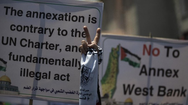 A Palestinian woman flashes the victory sign as she demonstrates against Israeli plans for the annexation of parts of the West Bank, in Gaza City, Wednesday, July 1, 2020. (AP Photo/Khalil Hamra)