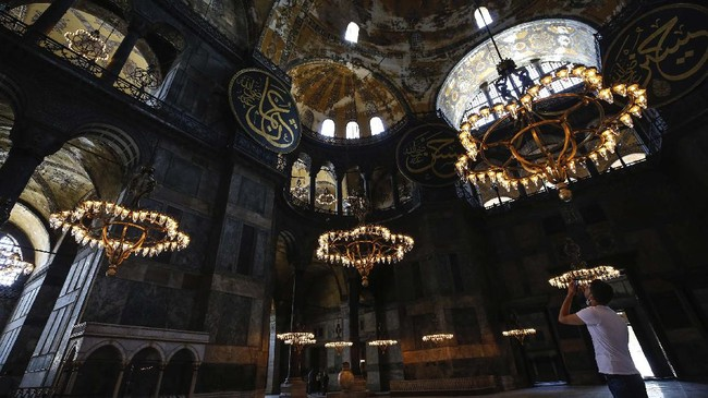 People visit the Byzantine-era Hagia Sophia, one of Istanbul's main tourist attractions in the historic Sultanahmet district of Istanbul, Thursday, June 25, 2020. The 6th-century building is now at the center of a heated debate between conservative groups who want it to be reconverted into a mosque and those who believe the World Heritage site should remain a museum. (AP Photo/Emrah Gurel)