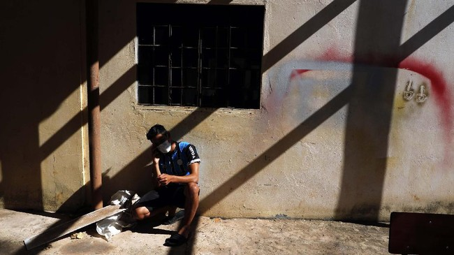 A young man talks on his cellphone in the patio area of a school being used as a government-run shelter where citizens returning home are required by law to quarantine for two weeks and pass two consecutive COVID-19 tests, as a preventive measure amid the COVID-19 pandemic in Ciudad del Este, Paraguay, Wednesday, June 24, 2020. There are 15,000 Paraguayans still waiting to reenter the country in neighboring nations like Brazil and Argentina. (AP Photo/Jorge Saenz)