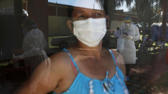 A woman in quarantine looks through the window to watch members of the National Mechanism to Prevent Torture (MNPT) visiting a school turned into a government-run shelter where citizens returning home are required by law to quarantine for two weeks and pass two consecutive COVID-19 tests as a preventive measure amid the COVID-19 in Ciudad del Este, Paraguay, Thursday, June 24, 2020. With only 7 million people, a stagnant economy, high poverty, and a weak public health system, Paraguay moved to slow coronavirus in March by closing borders and imposing the quarantine restrictions, along with closing schools and public events and declaring a nighttime curfew. (AP Photo/Jorge Saenz)