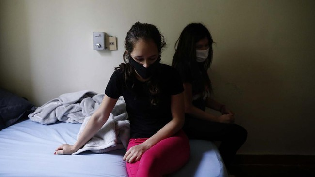 Women sit on a bed at a religious institution being used as a government-run shelter where citizens returning home are required by law to quarantine for two weeks and pass two consecutive COVID-19 tests, as a preventive measure amid the COVID-19 pandemic near Asuncion, Paraguay, Thursday, June 18, 2020. Along with Paraguay's relative isolation, experts credit the country's success at containing COVID-19 with creating a network of quarantine centers where citizens arriving home must isolate. (AP Photo/Jorge Saenz)