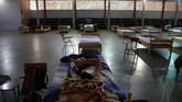 A youth rests on a bed with his cellphone at school turned into a government-run shelter where citizens returning home are required by law to quarantine for two weeks and pass two consecutive COVID-19 tests, as a preventive measure amid the COVID-19 pandemic in Ciudad del Este, Paraguay, Thursday, June 24, 2020. The youth said he was quarantined for 70 total days before he left. As nearby nations grapple with uncontrolled spread of the novel coronavirus, the small, poor, landlocked nation of Paraguay appears to be controlling the disease, with just a few thousand confirmed cases and a few dozen deaths. (AP Photo/Jorge Saenz)