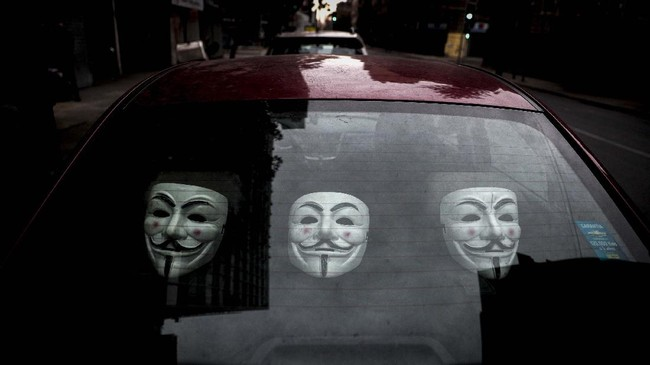 Guy Fawkes masks sit inside a car parked on a street in downtown Santiago, Chile, Sunday, June 28, 2020. (AP Photo/Esteban Felix)