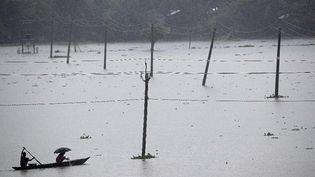 Villagers cross floodwaters on a country boat in Morigaon district of Assam, India, Friday, June 26, 2020. Following incessant rainfall, the Brahmaputra river and its tributaries continued to rise flooding several districts in the state. (AP Photo/Anupam Nath)