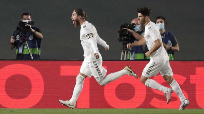 Real Madrid's Sergio Ramos, left, celebrates after scoring his side's opening goal from a penalty shot during the Spanish La Liga soccer match between Real Madrid and Getafe at the Alfredo di Stefano stadium in Madrid, Spain, Thursday, July 2, 2020. (AP Photo/Bernat Armangue)