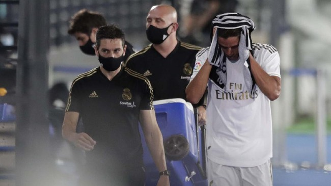 Real Madrid's Raphael Varane, right, leaves the field after injury during the Spanish La Liga soccer match between Real Madrid and Getafe at the Alfredo di Stefano stadium in Madrid, Spain, Thursday, July 2, 2020. (AP Photo/Bernat Armangue)
