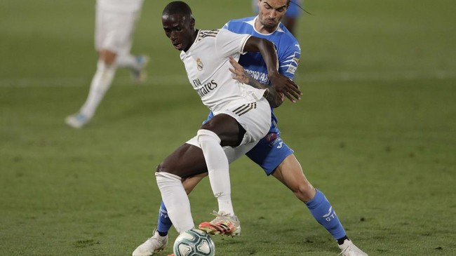 Real Madrid's Ferland Mendy, left, fights for the ball with Getafe's Jason during the Spanish La Liga soccer match between Real Madrid and Getafe at the Alfredo di Stefano stadium in Madrid, Spain, Thursday, July 2, 2020. (AP Photo/Bernat Armangue)
