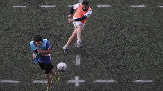 A man connects a shot during an amateur soccer match at a local club, Play Futbol 5, in Pergamino, Argentina, Wednesday, July 1, 2020. The club divided a soccer field into 12 rectangles to mark limited areas for each player, keeping them from making physical contact, an adaptation to continue playing amid government restrictions to curb the spread of the new coronavirus. (AP Photo/Natacha Pisarenko)