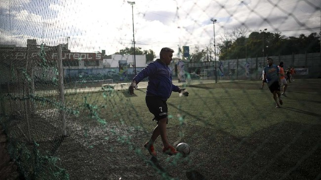 Martin Rodriguez controls the ball during an amateur soccer match at the Play Futbol 5 local club in Pergamino, Argentina, Wednesday, July 1, 2020. In order to continue playing amid government restrictions to curb the spread of the new coronavirus, the club divided its soccer field into 12 rectangles to mark limited areas for each player, keeping them from making physical contact. (AP Photo/Natacha Pisarenko)