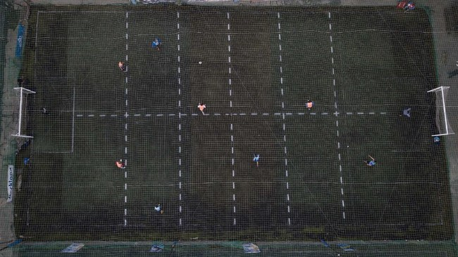 Men play soccer at a local club, Play Futbol 5, in Pergamino, Argentina, Wednesday, July 1, 2020. In order to continue playing amid government restrictions to curb the spread of the new coronavirus, the club divided its soccer field into 12 rectangles to mark limited areas for each player, keeping them from making physical contact. (AP Photo/Natacha Pisarenko)