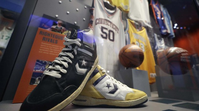Basketball shoes once belonging to Boston Celtics' Larry Bird, front left, and Los Angeles Lakers' Magic Johnson rest together in a display case at the Naismith Memorial Basketball Hall of Fame, in Springfield, Mass., Tuesday, June 23, 2020. The museum is scheduled to reopen in the beginning of July 2020 with a whole new look after a $22 million renovation.  (AP Photo/Steven Senne)