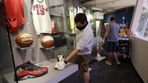 Alex Pedro, front, a curatorial assistant at the Naismith Memorial Basketball Hall of Fame, places a basketball shoe once belonging to Los Angeles Lakers' Kobe Bryant into an exhibit at the museum, in Springfield, Mass., Tuesday, June 23, 2020. The museum is scheduled to reopen in the beginning of July 2020 with a whole new look after a $22 million renovation. After delaying the unveiling because of the coronavirus pandemic, the building will reopen with new social distancing measures in place. (AP Photo/Steven Senne)