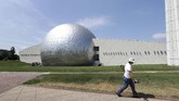 A worker carries a shovel in front of the Naismith Memorial Basketball Hall of Fame in Springfield, Mass., Tuesday, June 23, 3030. The museum is scheduled to reopen in the beginning of July 2020 with a whole new look after a $22 million renovation. (AP Photo/Steven Senne)