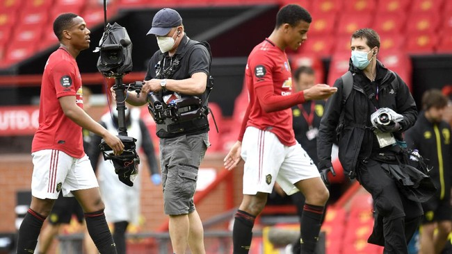 A television crew wears face masks while capturing footage during the English Premier League soccer match between Manchester United and Bournemouth at Old Trafford stadium in Manchester, England, Saturday, July 4, 2020. (Peter Powell/Pool via AP)