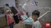 Petugas medis menggunakan alat pelindung diri (APD) saat memeriksa gigi pasien anak di salah satu klinik gigi di daerah Ceger, Jakarta, Sabtu, 4 Juli 2020. CNN Indonesia/Bisma Septalisma