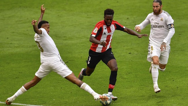 Athletic Bilbao's Inaki Williams, center, duels for the ball with Real Madrid's Eder Militao, left, and Real Madrid's Sergio Ramos during the Spanish La Liga soccer match between Athletic Club and Real Madrid at the San Manes stadium in Bilbao, Spain, Sunday, July 5, 2020. (AP Photo/Alvaro Barrientos)