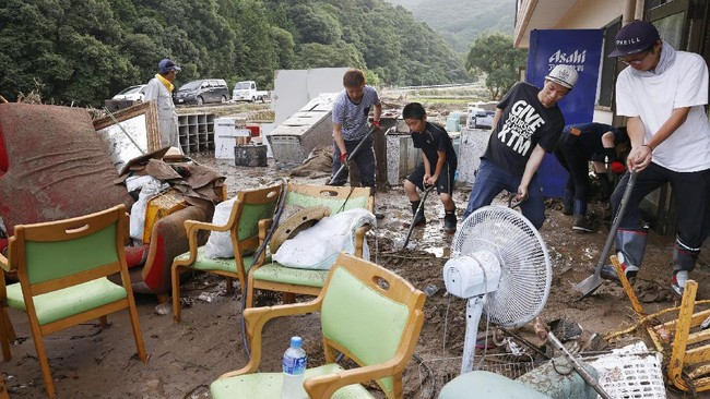 Workers try to clean their nursing home following a heavy rain in Ashikita town, Kumamoto prefecture, southern Japan Saturday, July 4, 2020. Heavy rain in southern Japan triggered flooding and mudslides on Saturday, leaving more than a dozen people presumed dead, some missing and dozens stranded on rooftops waiting to be rescued, officials said. (Takuto Kaneko/Kyodo News via AP)