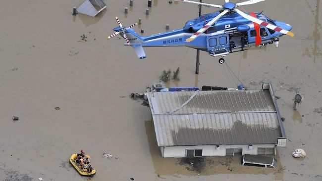 Rescue operation is conducted in a flooded area following a heavy rain in Hitoyoshi, Kumamoto prefecture, southern Japan Saturday, July 4, 2020. Heavy rain in southern Japan triggered flooding and mudslides on Saturday, leaving more than a dozen people presumed dead, some missing and dozens stranded on rooftops waiting to be rescued, officials said. (Kyodo News via AP)