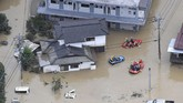 Rescue operation is conducted in a flooded area in Hitoyoshi, Kumamoto prefecture, southern Japan Saturday, July 4, 2020. Heavy rain in southern Japan triggered flooding and mudslides on Saturday, leaving more than a dozen people presumed dead, some missing and dozens stranded on rooftops waiting to be rescued, officials said. (Kyodo News via AP)