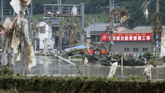 Japan Ground Self-Defense Force members evacuate people to a safer place by boat in Kuma village, Kumamoto prefecture, southwestern Japan, Sunday, July 5, 2020. Heavy rain in the Kumamoto region triggered flooding and mudslides Saturday and left dozens still being stranded at their homes and other facilities. (Kyodo News via AP)