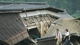 A couple walks in front of houses damaged by flood in Kuma village, Kumamoto prefecture, southwestern Japan, Sunday, July 5, 2020. Heavy rain in the Kumamoto region triggered flooding and mudslides Saturday and left dozens still being stranded at their homes and other facilities. (Koji Harada/Kyodo News via AP)
